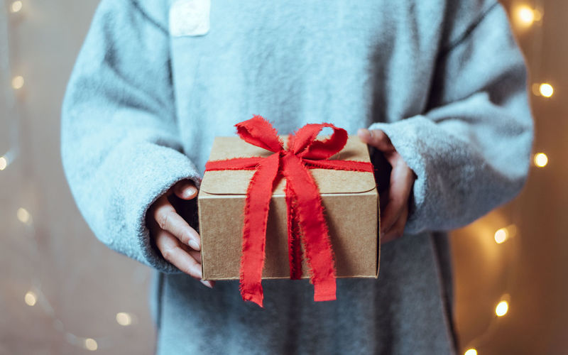 Midsection of woman holding gift box with red bow tie