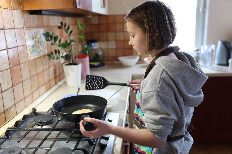 A girl cooks pancakes in the kitchen