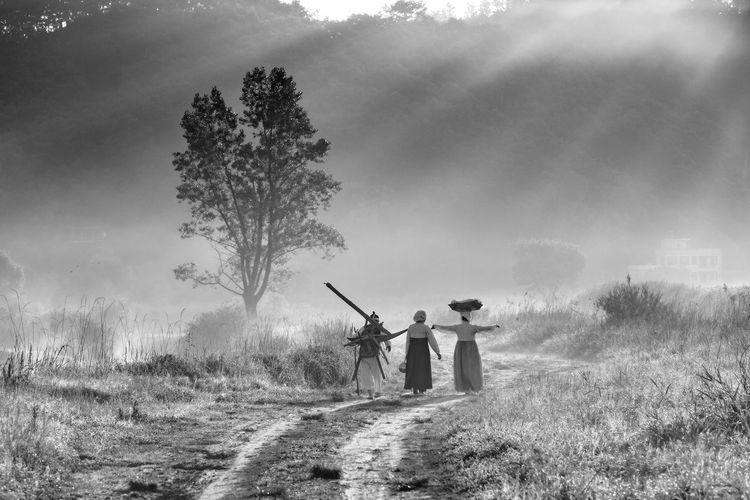 Women walking on field against sky