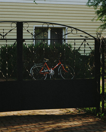 Bicycle parked by fence against building