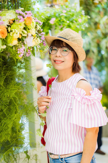 lady posting in the garden Flower Flowering Plant Plant Real People Leisure Activity One Person Standing Lifestyles Women Nature Young Women Glasses Casual Clothing Young Adult Holding Hat Vulnerability  Three Quarter Length Fashion Beautiful Woman Hairstyle Outdoors