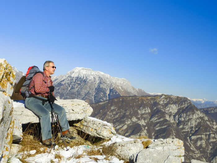Man sitting on rock while hiking on mountain against sky