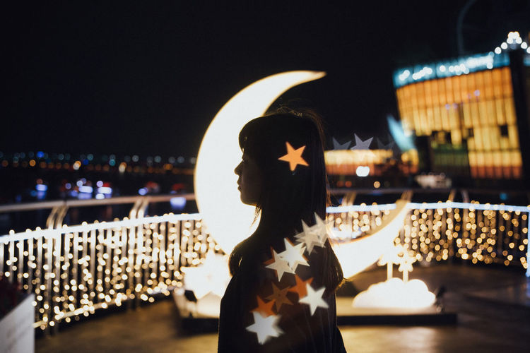 Side view of young woman standing on illuminated building terrace against clear sky at night