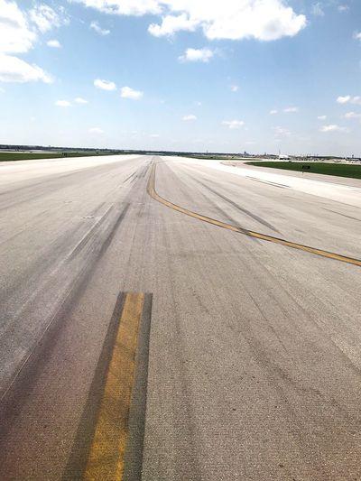 Road passing through airport runway against sky