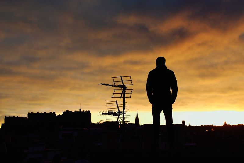 Silhouette man standing on rooftop against sky during sunrise