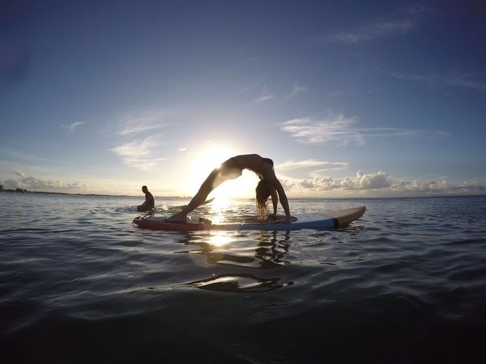Full length of woman exercising on surfboard at lake against sky during sunset