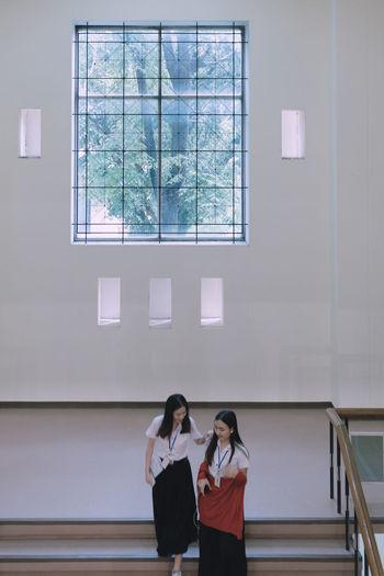 Rear view of women standing by window