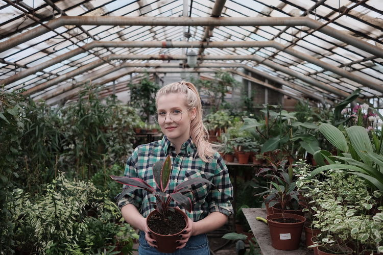 Portrait of smiling woman standing in greenhouse
