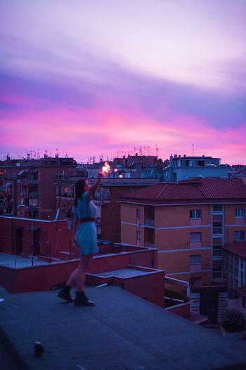 Full length of illuminated town against sky during sunset