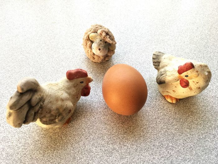 High angle view of her figurines with brown egg on table