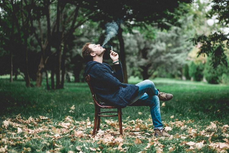 Side view of man sitting on bench in park