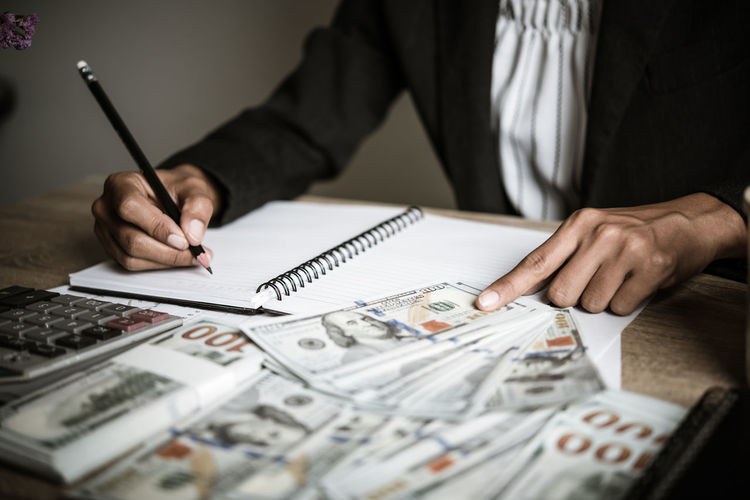 Midsection of businessman writing in book while counting money on table