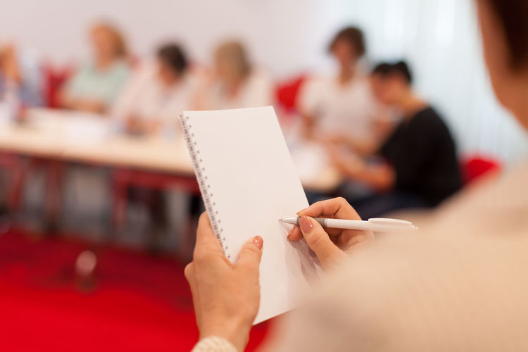 Cropped image of woman writing on spiral notebook during seminar