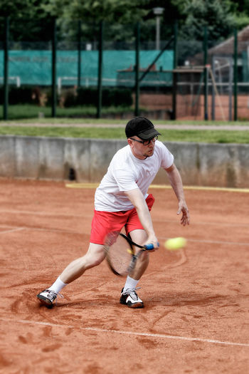 Mature man playing tennis at court