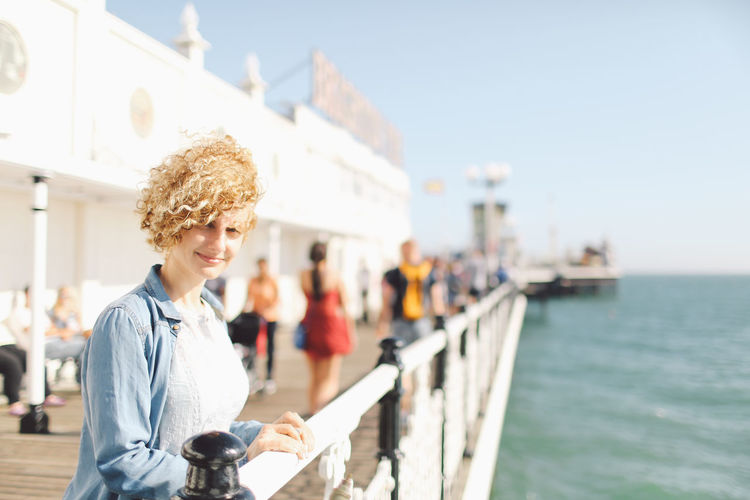 Portrait of woman at brighton pier against sky