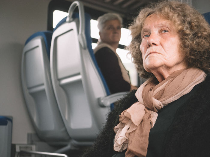 Portrait of woman with arms raised in bus