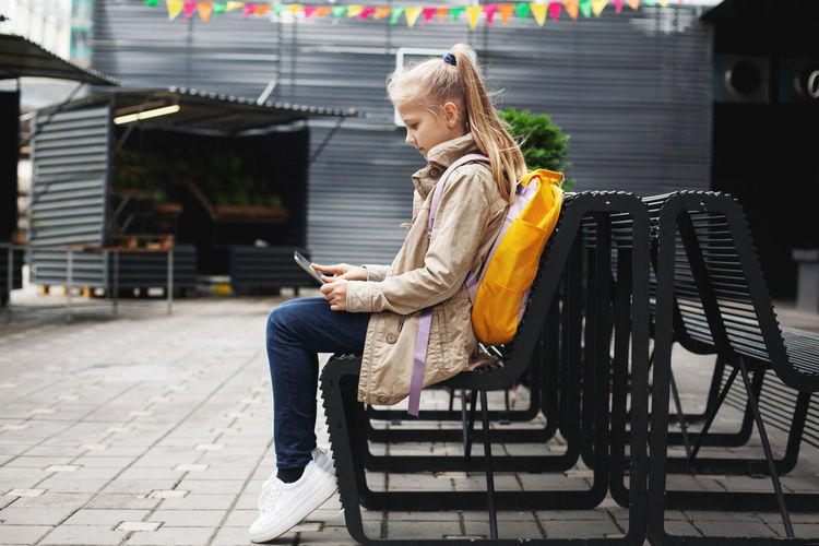 After school, a cute girl sits on a bench waiting for the bus, studies on a tablet online