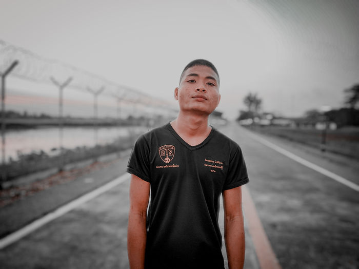 Portrait of young man standing on road against sky