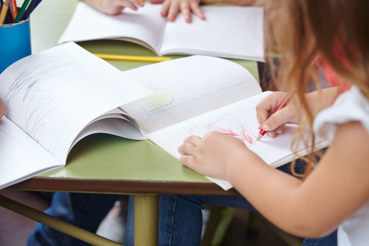 Midsection of girl drawing in book on table