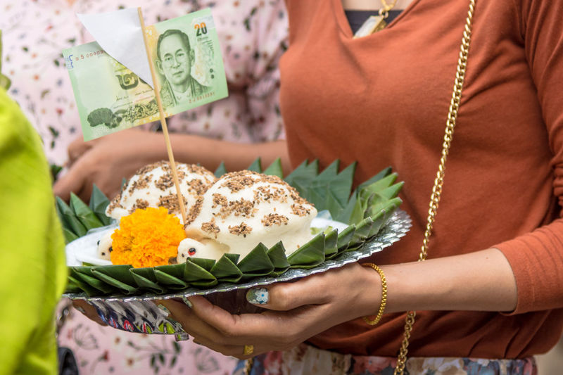 Midsection Of Woman Holding Religious Offerings With Paper Currency