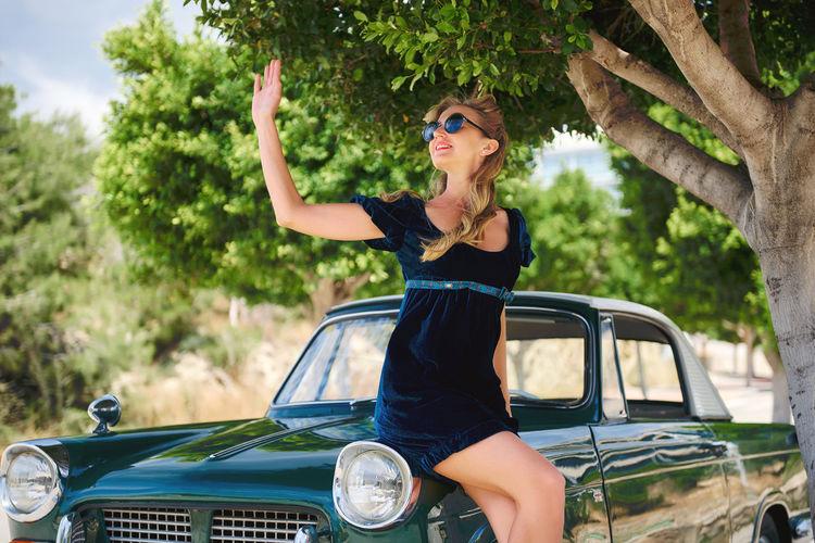 Mid adult woman sitting on vintage car by tree
