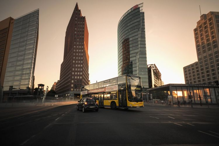 Cars on road amidst buildings against sky during sunset