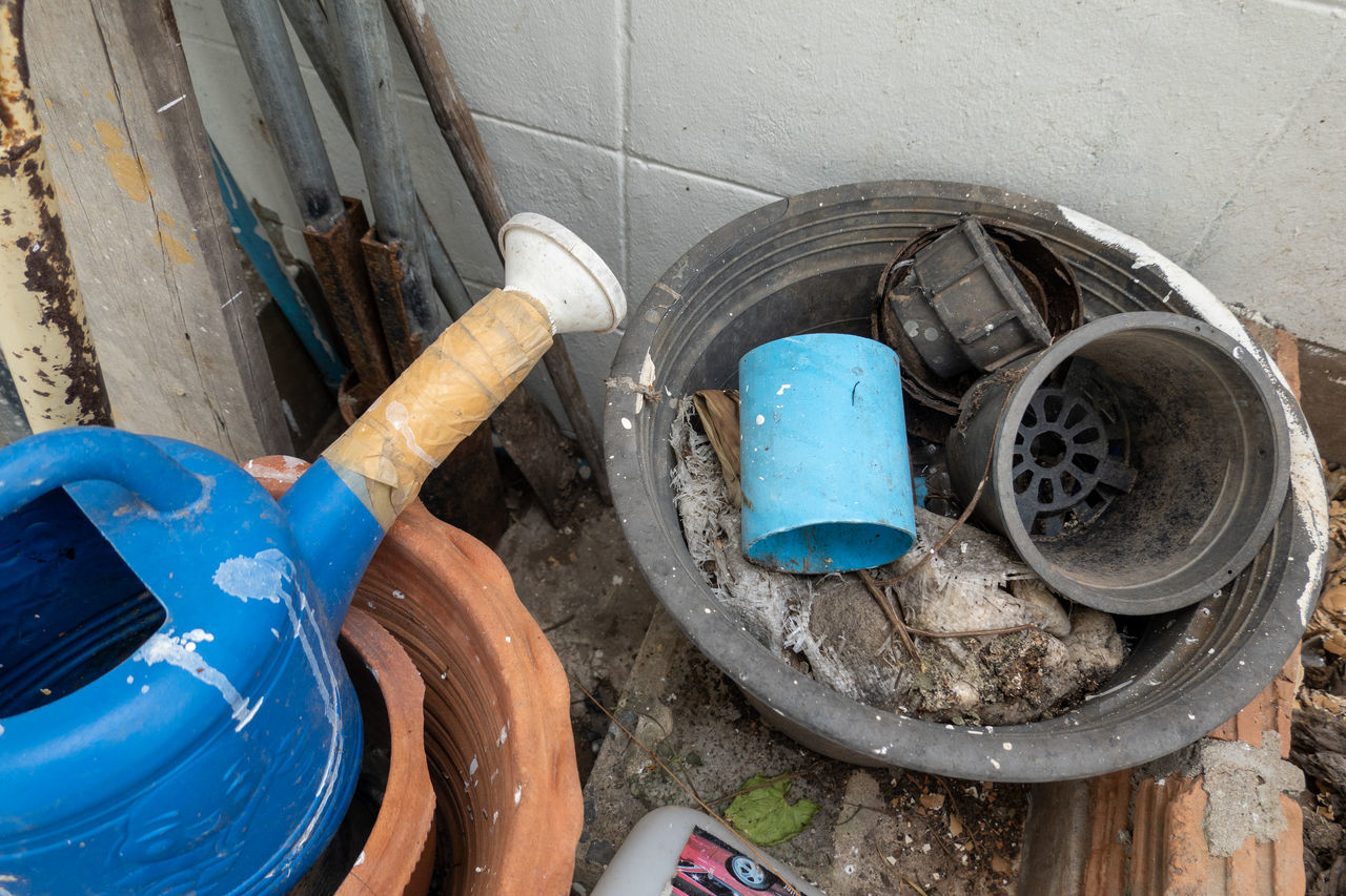 HIGH ANGLE VIEW OF MESSY CONTAINER ON FLOOR