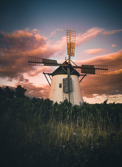 Traditional windmill on field against sky during sunset