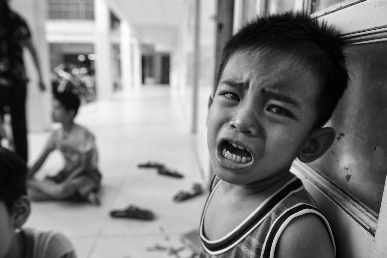 Portrait of boy crying in corridor