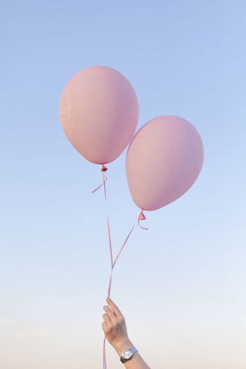 Low angle view of woman holding pink helium balloons against sky