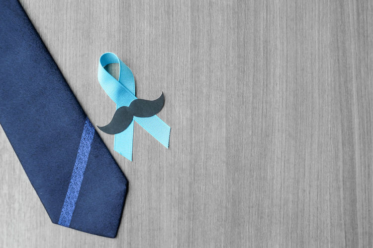 Directly above view of blue ribbon with mustache by necktie on table
