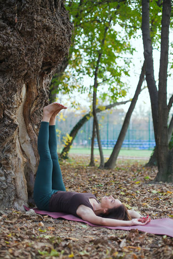 Side view of woman relaxing on tree trunk