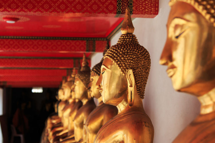 Golden buddha statues in row at wat pho temple