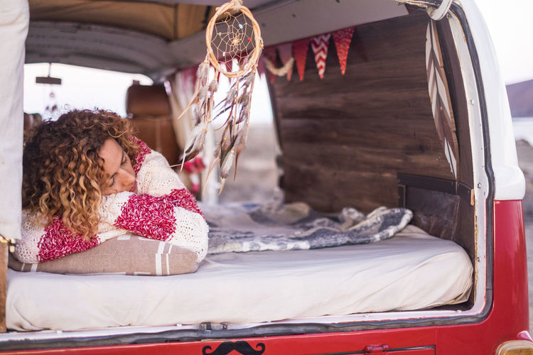 Young Woman Sleeping On Bed In Caravan