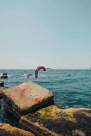 Full length of teenage boy diving in sea against sky