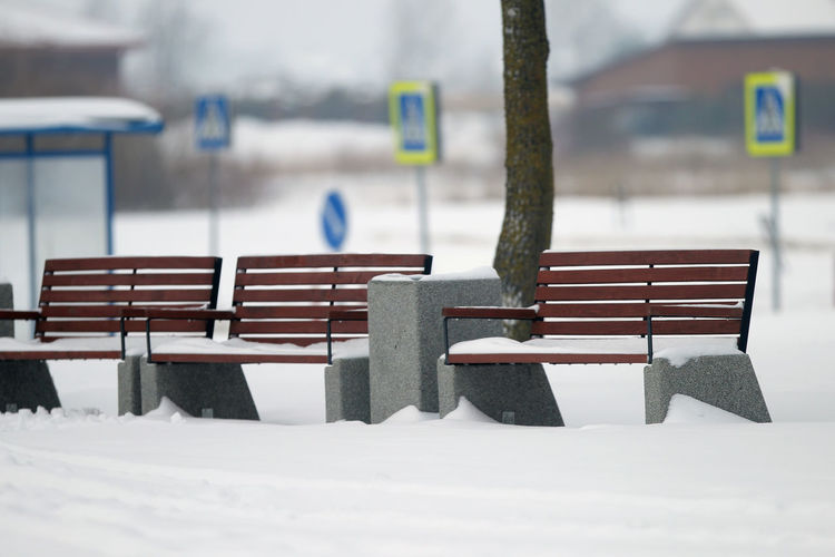 Empty chairs and tables in snow