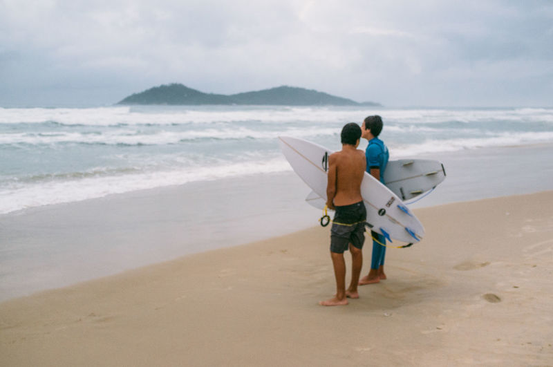 Beach Beauty In Nature Brazil Cloud Florianópolis Horizon Over Water Leisure Activity Men Nature Outdoors Real People Rear View Sand Scenics Sea Shore Sky Surf Surfers Surfing Togetherness Two People Vacations Walking Wave