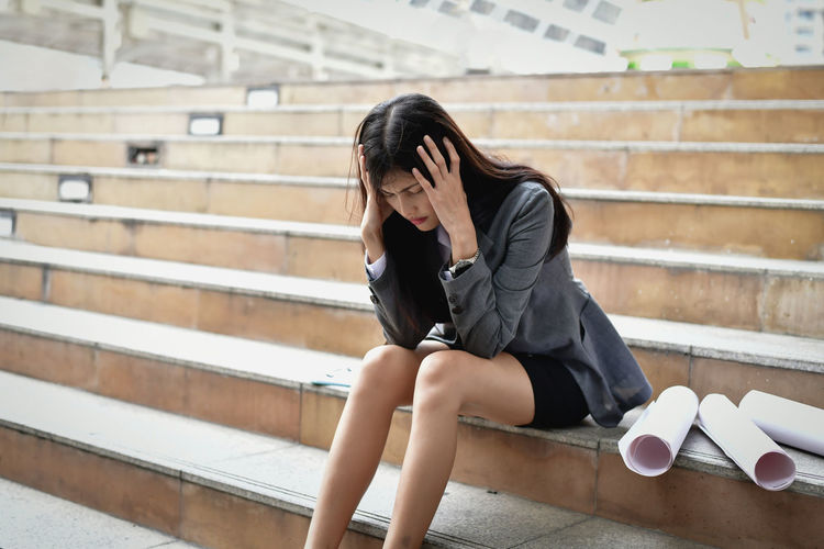 Stressed businesswoman with head in hands sitting on steps