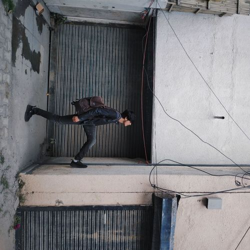 Optical illusion of young man walking on wall