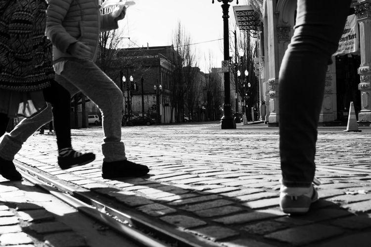Low section of women walking on sidewalk in city