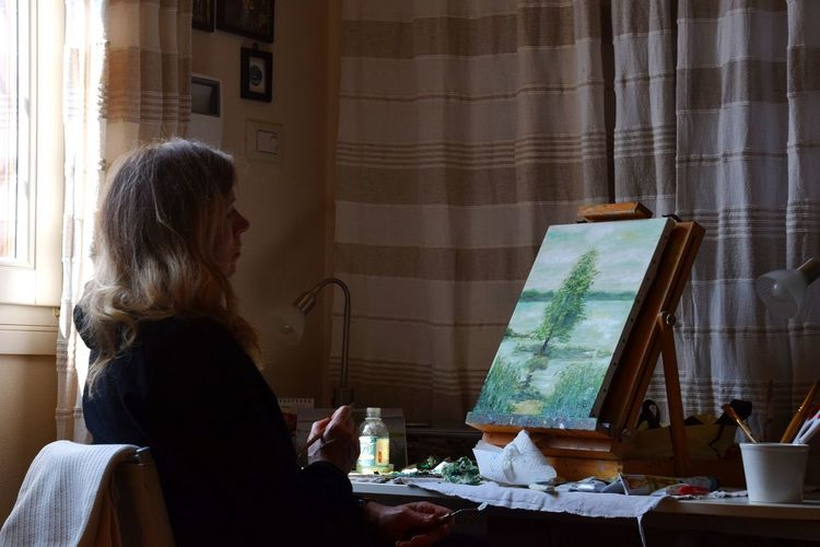 Side view of woman sitting at home