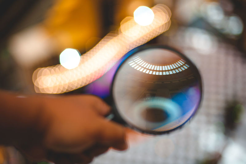 Close-up of person holding magnifying glass