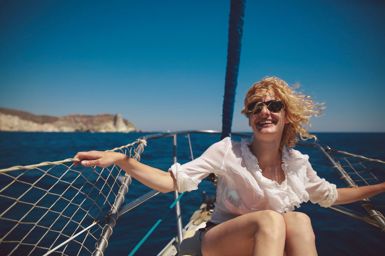 Cheerful mid adult woman sitting on sailboat in sea during summer