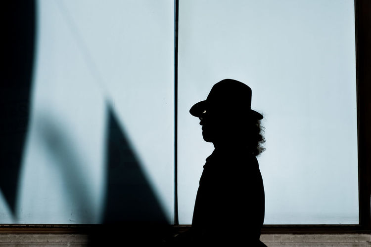 Silhouette man wearing hat standing against wall