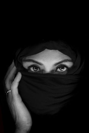 Portrait of beautiful woman against black background