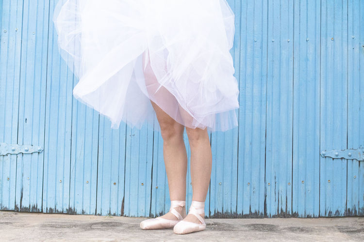 Low Section Of Ballet Dancer Wearing Dress While Standing Against Wood Paneling