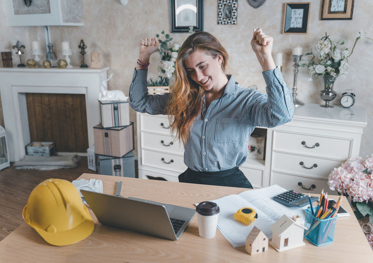 Woman standing by table at home