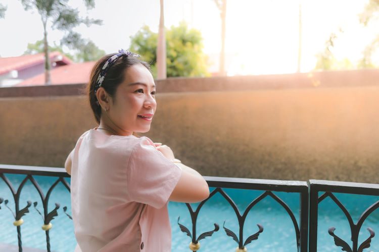 Portrait of smiling woman standing by railing