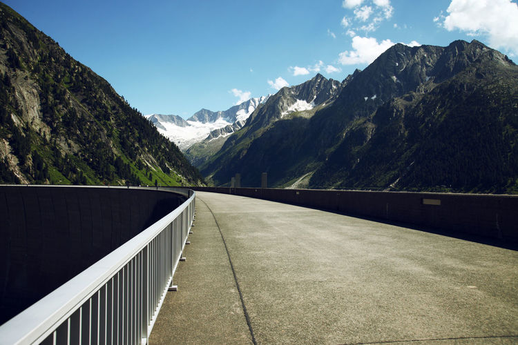 Beauty In Nature Cloud - Sky Crash Barrier Day Environment Mountain Mountain Peak Mountain Range Nature No People Non-urban Scene Outdoors Plant Railing Road Scenics - Nature Sky Sunlight The Way Forward Tranquil Scene Tranquility Transportation