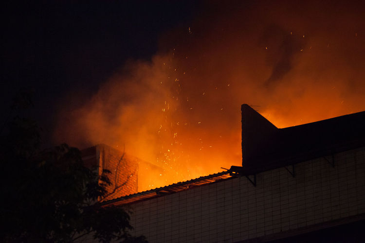 Low angle view of building under fire at night